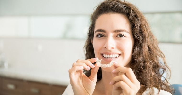 A woman putting in her Invisalign aligner to speed up treatment